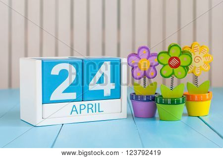 April 24th. Image of april 24 wooden color calendar on white background with flowers. Spring day, empty space for text. World Immunization Week.