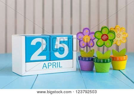 April 25th. International Day Of DNA. Image of april 25 wooden color calendar on white background with flowers. Spring day, empty space for text.
