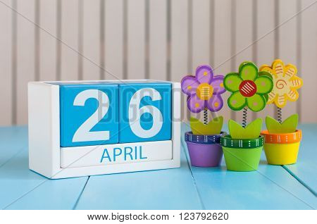 April 26th. Image of april 26 wooden color calendar on white background with flowers. Spring day, empty space for text.