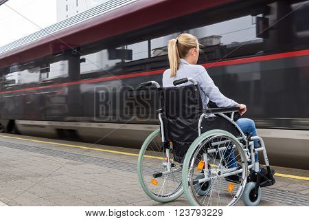 woman sitting in a wheelchair at a train station