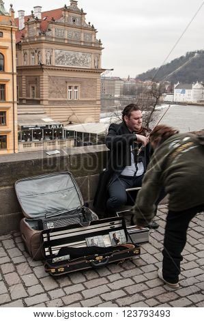 PRAGUE, CZECH REPUBLIC - FEBRUARY 13, 2016:  Street musician on the Charles Bridge