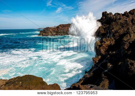 Volcanic Los Hervideros coastline with wavy ocean and blue sky on Lanzarote island in Spain