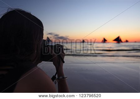Woman taking photographs of yachts sailing in tropical sea at sunset