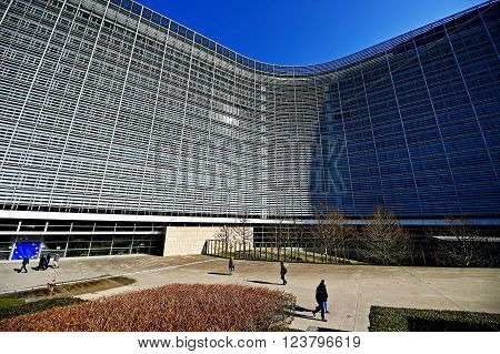 BRUSSELS BELGIUM - MARCH 16: People walk by the European Commission Headquarters also know as the Berlaymont building on March 16 2016 in Brussels.
