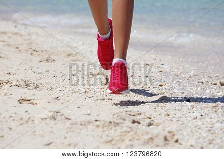 Close-up view of Running woman feet jogging on beach