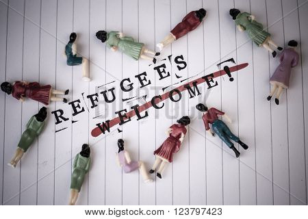refugees welcome strikethroughtext on white line paper with face off woman figures around