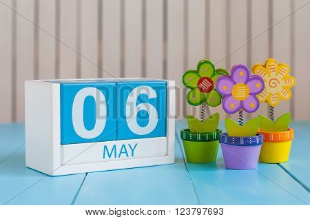 May 6th. Image of may 6 wooden color calendar on white background with flowers. Spring day, empty space for text.