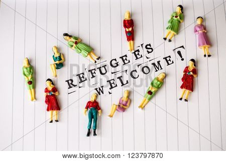 refugees welcome text on white line paper with woman figures around