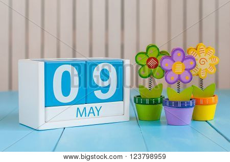May 9th. Image of may 9 wooden color calendar on white background with flowers. Spring day, empty space for text.  Symbols Of the victory in World War II.