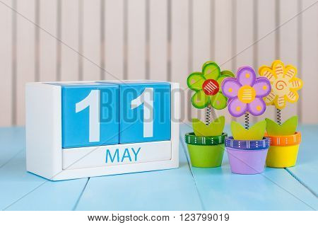 May 11th. Image of may 11 wooden color calendar on white background with flower. Spring day, empty space for text.