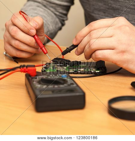 Repairer Looking For A Fault In The Phone With A Multimeter.