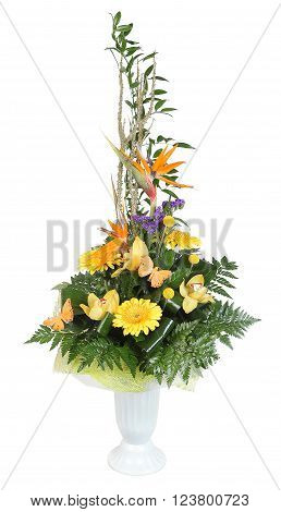 Bouquet of flowers in plastic vase yellow gerbera daisies and pale yellow orchids decorated with ferns isolated on white background.