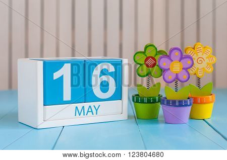 May 16th. Image of may 16 wooden color calendar on white background with flowers. Spring day, empty space for text.  Biographers Day.