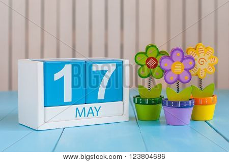 May 17th. Image of may 17 wooden color calendar on white background with flowers. Spring day, empty space for text.  International Day Against Homophobia, IDAHOBIT.