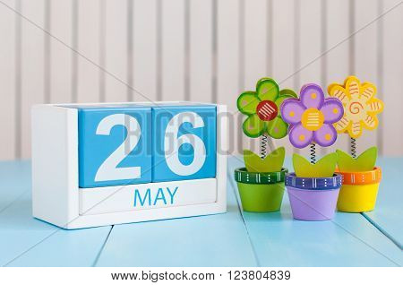 May 26th. Image of may 26 wooden color calendar on white background with flowers. Spring day, empty space for text.
