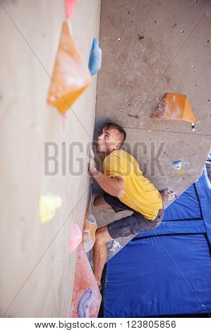 Young man climber on artificial climbing wall