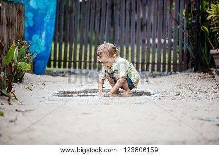 Cute barefoot boy plunging hands in puddle and watching water