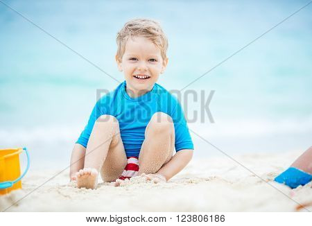 Cute little boy playing on the tropical beach