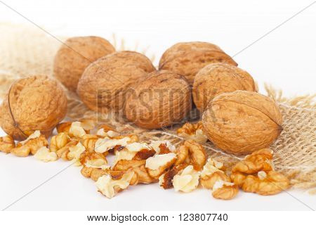 walnuts broken on jute with white background
