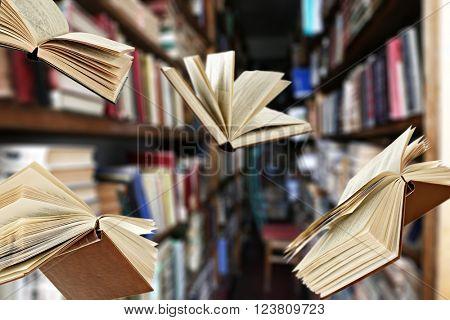 Flying books on library bookshelves background