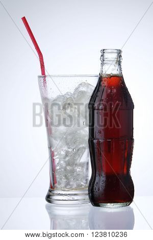 bottle of cola soda and glass of ice  isolated on a white background