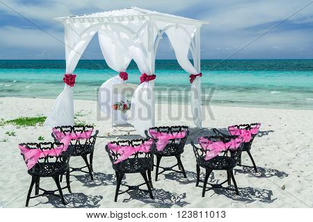 Beautiful, amazing gorgeous inviting view of wedding decorated gazebo with old vintage black metal chairs on the beach against tranquil turquoise ocean
