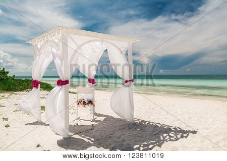 Beautiful, amazing gorgeous inviting view of wedding decorated gazebo against tranquil turquoise tender ocean and blue sky background