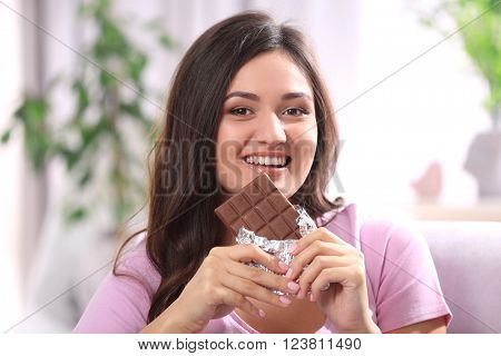 Portrait of beautiful young brunette with chocolate on sofa in the room , close up