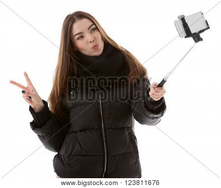 Young attractive girl in winter clothing making photo by her self with mobile phone, isolated on white