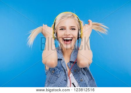 Cheerful female teenager holding her ponytails over blue background