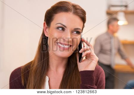 Close up shot of a young woman talking over phone. Happy businesswoman talking on mobile phone. Portrait of smiling businesswoman talking on cellphone sitting at the office.