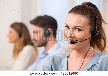 Portrait of young business woman in a call center office. Smiling customer support operator at work. Portrait of young call center operator wearing headset with colleagues working in background.