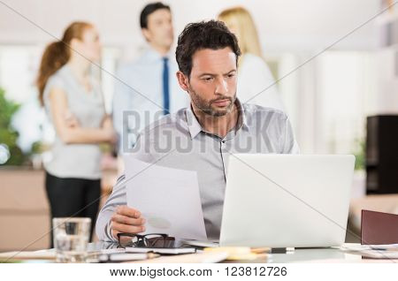 Serious businessman typing information on laptop with reference of documents. Businessman counting financial data while working on laptop in office. Man working at office.
