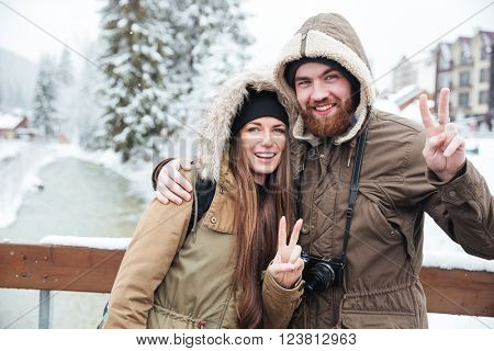 Happy young couple with photo camera stading and showing peace gesture on winter resort