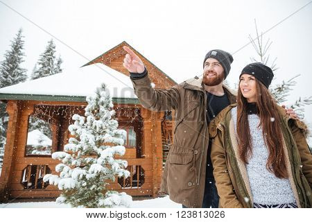 Handsome smiling bearded young man stading with his girlfriend near log cabin and pointing away