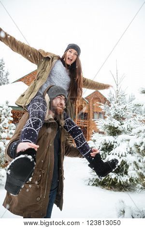 Hadsome smiling bearded young man carrying his girlfriend on shoulders in winter