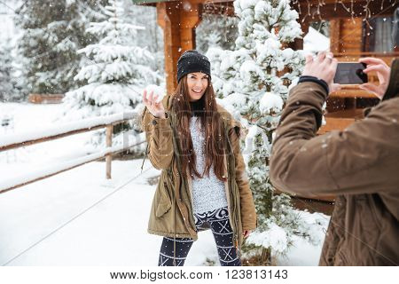 Smiling pretty young woman standing and posing to her boyfriend taking pictures of her with smartphone in snowy weather