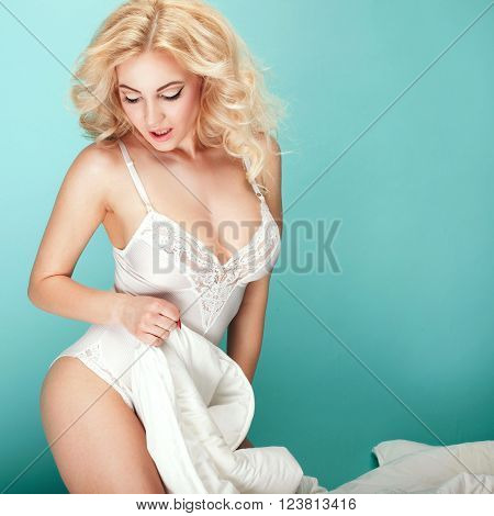 Blonde sensual woman posing in white lingerie over flying feathers. STudio shot.