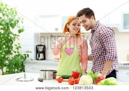 Happy couple cooking salad on the kitchen. Man tasting a dish