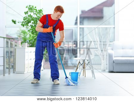 Young janitor with brush and bucket cleaning floor in office