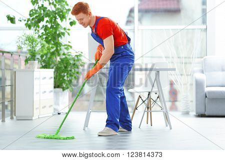 Young janitor with brush cleaning floor in office