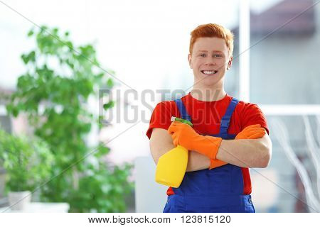 Young janitor holding liquid detergent in office