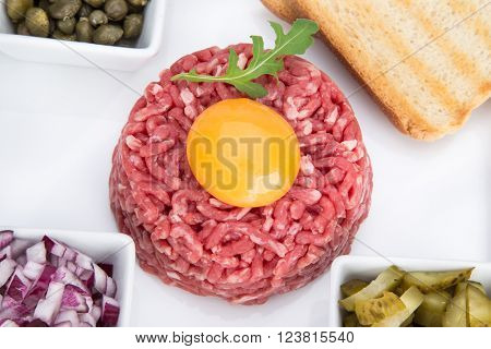 Close up of beef tartar with capers and small toasts.