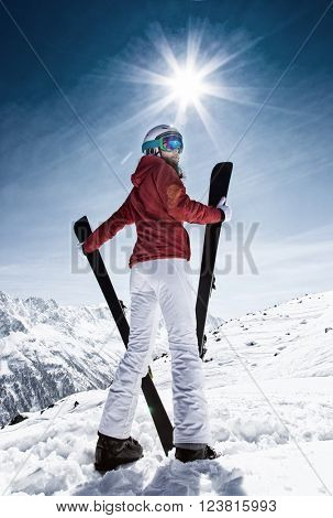 Young woman with ski on mountains during sunny day.