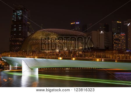 Singapore - Mar 26, 2016: Night view of white Jubilee Bridge with a belt of green light projection under and the Esplanade Building.