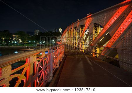 Singapore - Mar 26, 2016: White Anderson Bridge over Singapore River was lightened up by lamps in red, yellow and green.