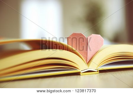 Book and heart shaped bookmark on a wooden table
