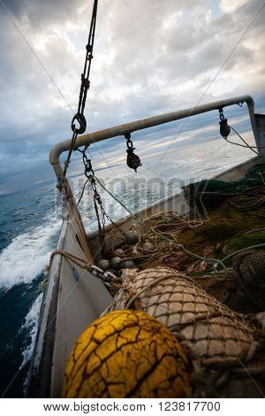 Fishing nets and rigging at the stern of a fishing vessel. Evening time.