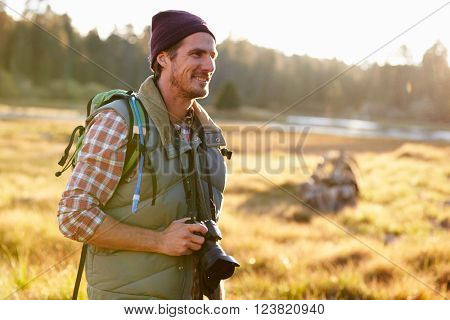 Man Hiking with camera in countryside