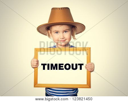 Little Funny girl in striped shirt with blackboard. Text TIMEOUT. Isolated on gray background.